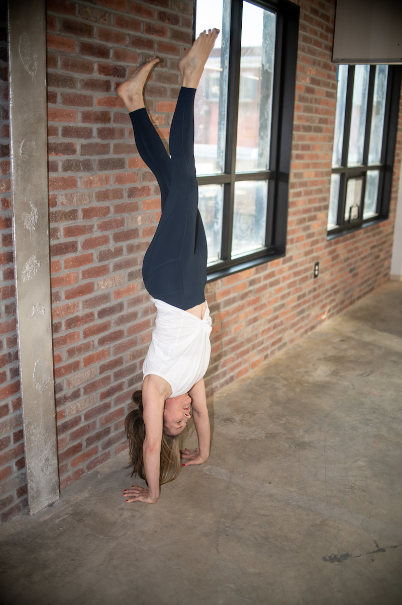 Blond woman in white shirt and black pants is inverted in a handstand next to a brick wall