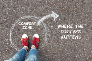"""Feet in red sneakers stand in a chalk circle on a sidewalk- the words """"comfort zone"""" are written in the circle and an arrow points out of the circle to the words """"where the success happens""""."""