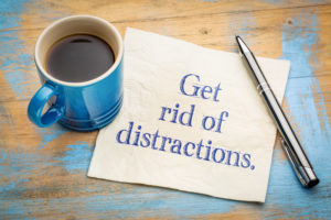 Blue mug of coffee sits on a napkin that says 'get rid of distractions' in blue letters with a pen on the side.