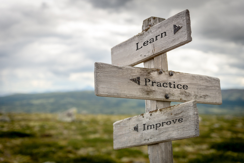 Wooden sign post outside that says Learn, Practice, Improve