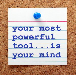 """Note posted on a cork board with a blue tack that reads """"your most powerful tool...is your mind"""" in blue on white."""