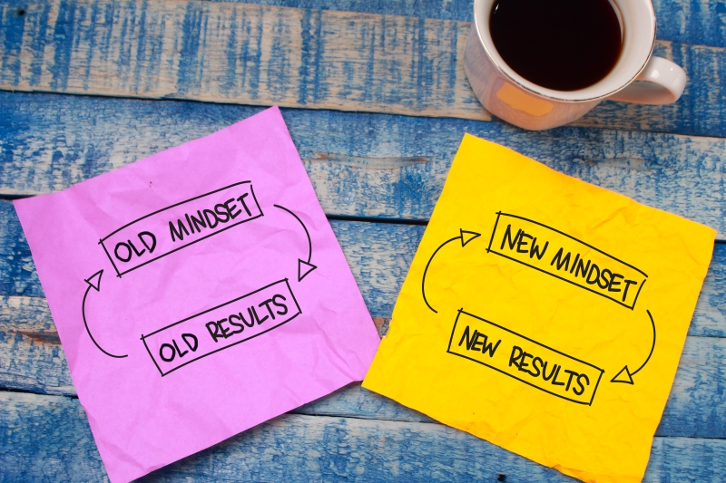 Two papers on a table with a coffee cup. One paper says old mindset old results and the other says new mindset new results.