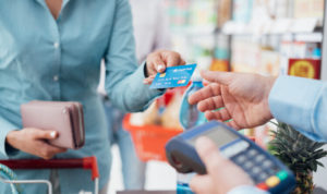 Woman in a blue shirt hands over a blue credit card at a store checkout.