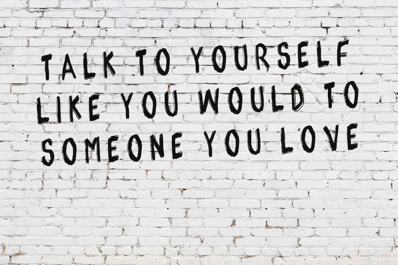 against a white brick wall is the phrase 'talk to yourself like you would to someone you love'
