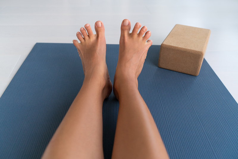 Woman's feet stretching and spreading toes doing toe stretch on exercise mat of living room floor at home.