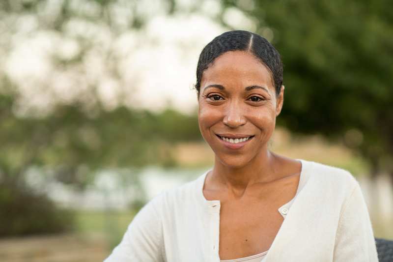 Mature confident African American woman in a white shirt smiling outside