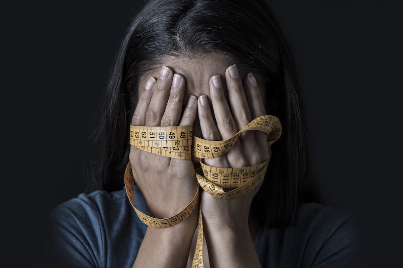 Close up hands wrapped in a measuring tape covering face of young depressed and worried woman.