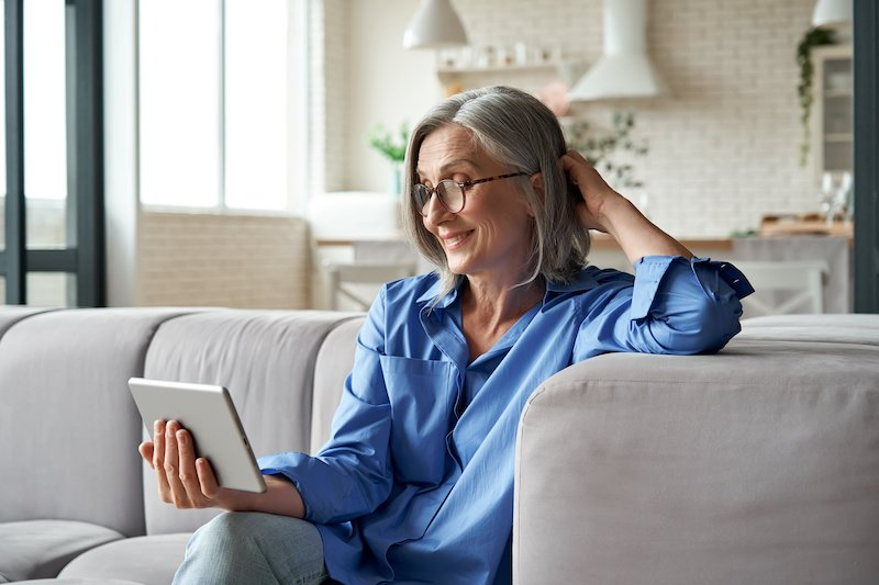 Woman on couch reading iPad