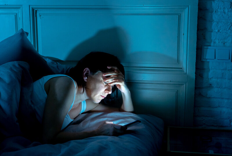 Woman with brown hair is lying in bed looking at her phone in the dark. The lighting is blue from the screen.