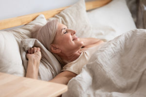 Mature woman waking up in a bed with white sheets and pillows.
