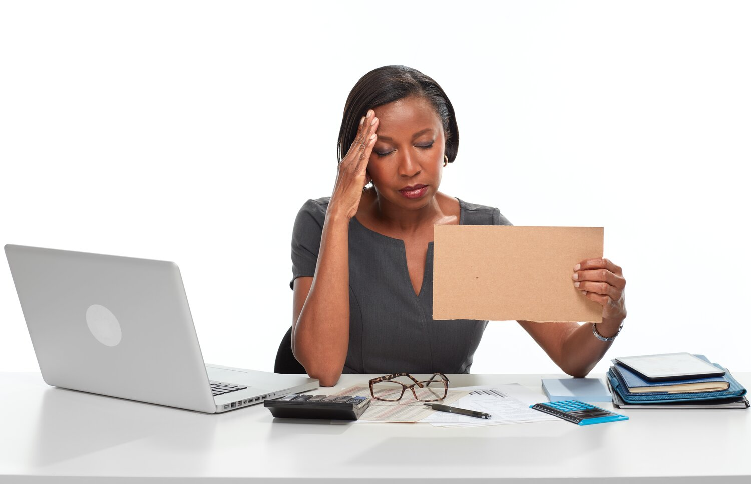 African American business woman looks tired and stressed with her hand to her forehead. She is surrounded by a laptop, glasses, calculator, and papers.