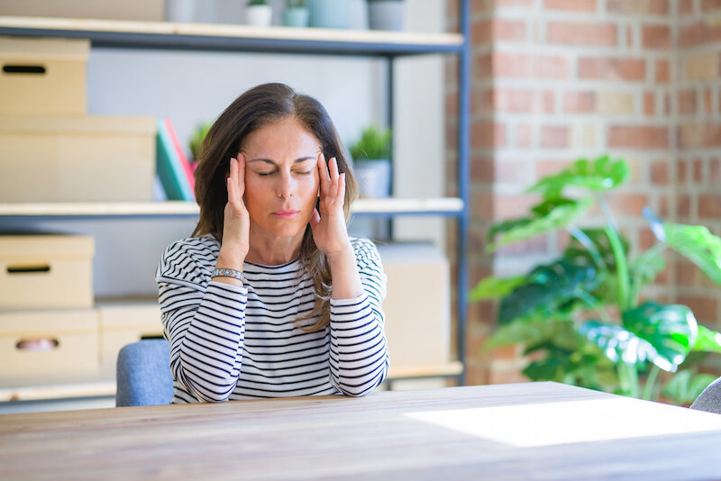 Middle age senior woman sitting at the table at home with hand on head for pain in head because stress.