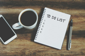 """Smart phone, coffee, pen and notepad with text """"to do list"""" sitting on a wooden table."""